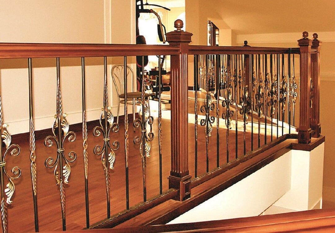 Деревянное ограждение второго этажа и лестничной площадки с элементами ковки